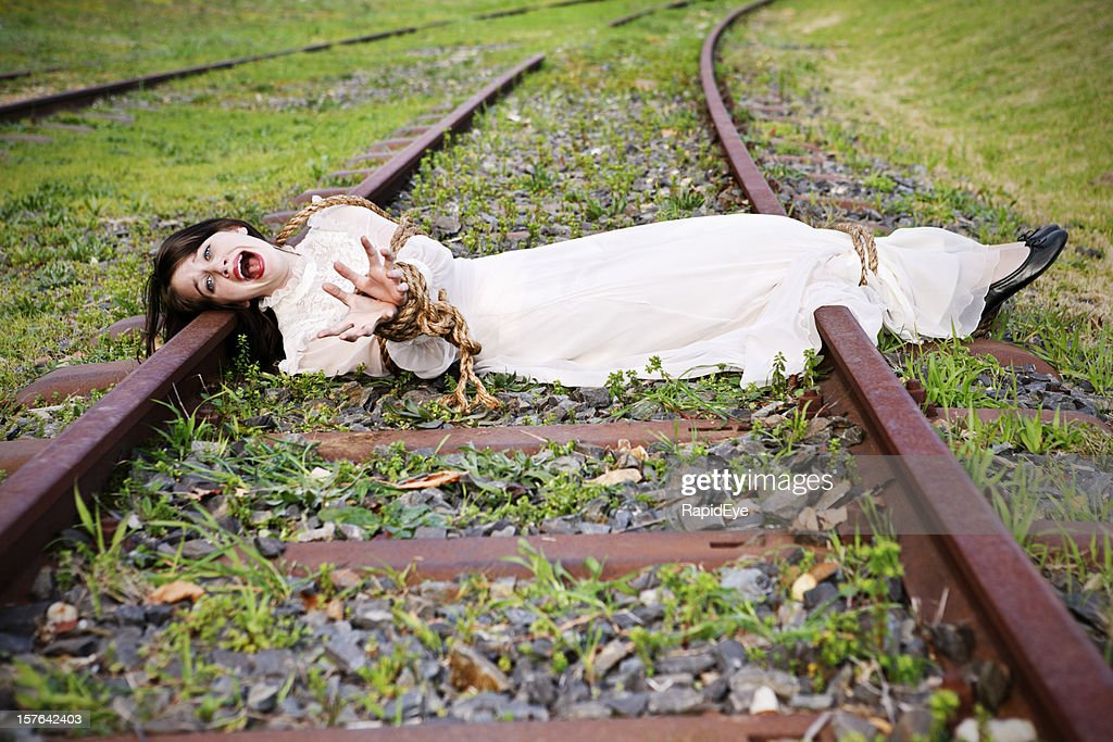 Woman in period dress lies bound and screaming on railtrack : Stock Photo