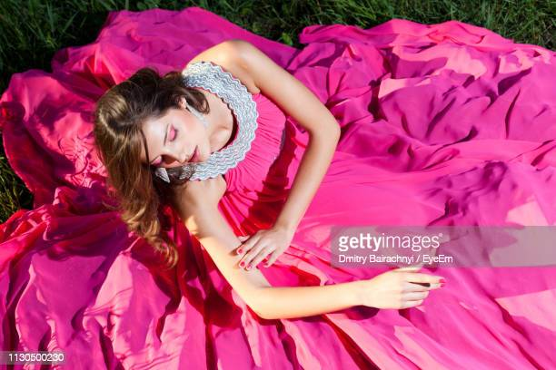 woman in pink gown sitting on field - イブニングドレス ストックフォトと画像