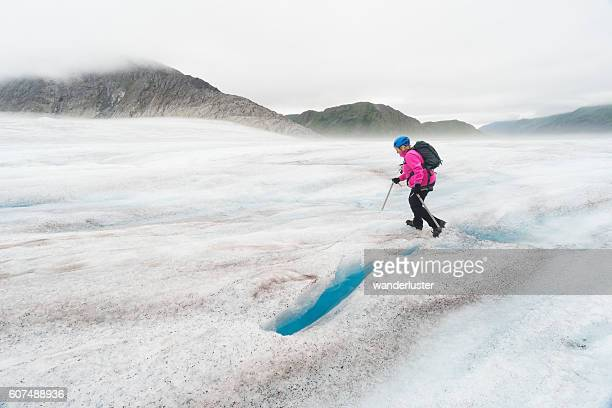 Woman in pink hikes across glacier
