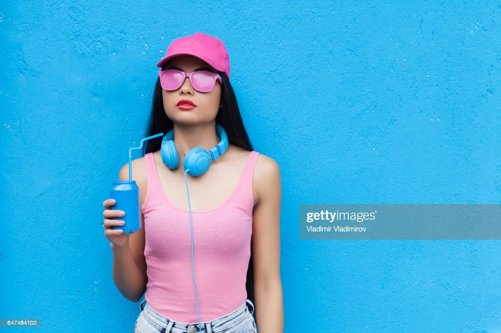 Woman in pink outfit holding blue can : Stock Photo