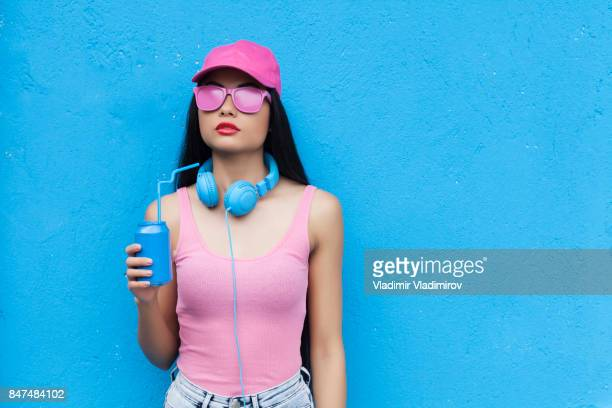 woman in pink outfit holding blue can - asian drink stock photos and pictures