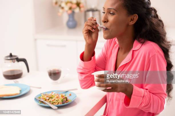 a woman in pink pajama eating yogurt in the morning. - beautiful israeli women stock pictures, royalty-free photos & images