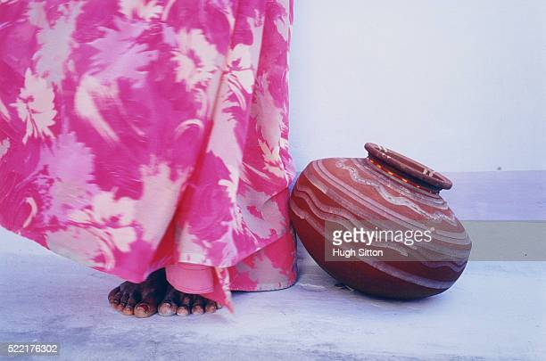 woman in pink sari standing beside a jug, india - hugh sitton stockfoto's en -beelden
