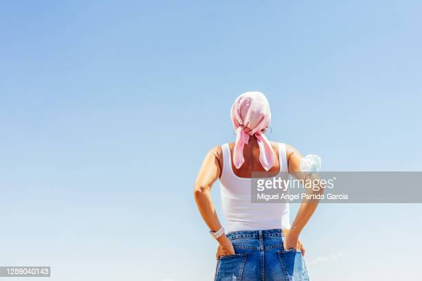 woman in pink scarf with cancer with hands in pockets and a protective mask on her arm - hände in den taschen stock-fotos und bilder