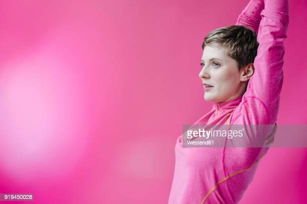 woman in pink sportswear stretching her arms - sportlerin stock-fotos und bilder