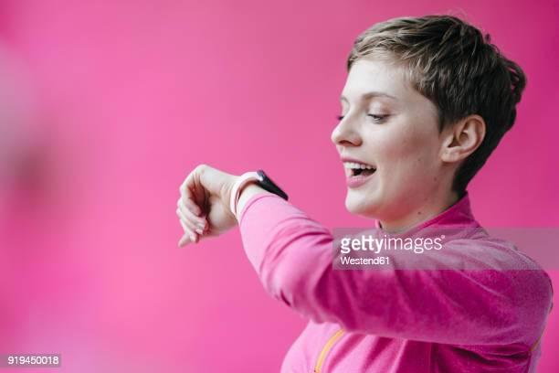 Woman in pink sportswear wearing smartwatch
