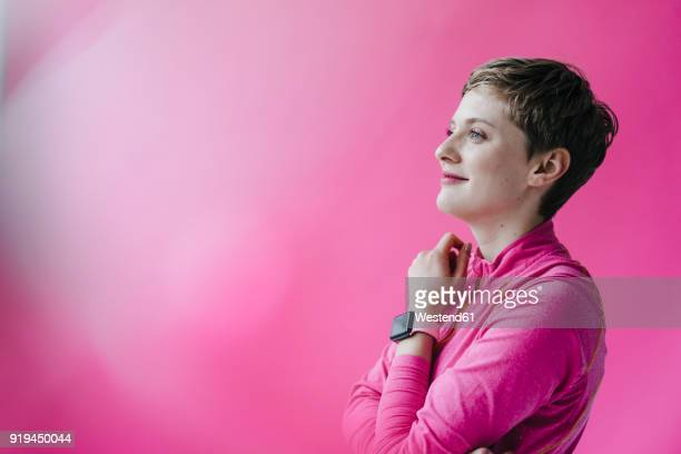Woman in pink sportswear wearing smartwatch