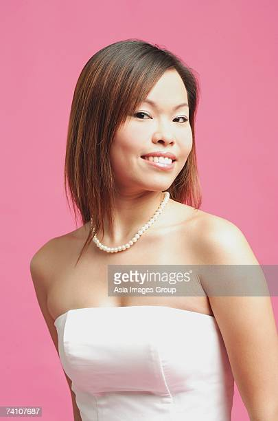 Woman in pink tube top and pearl necklace