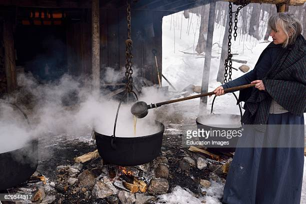 Woman in pioneer clothes ladling evaporated sap in cast iron pots to produce maple syrup