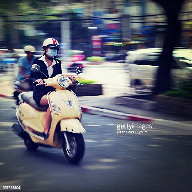 Woman In Pollution Mask Driving Scooter