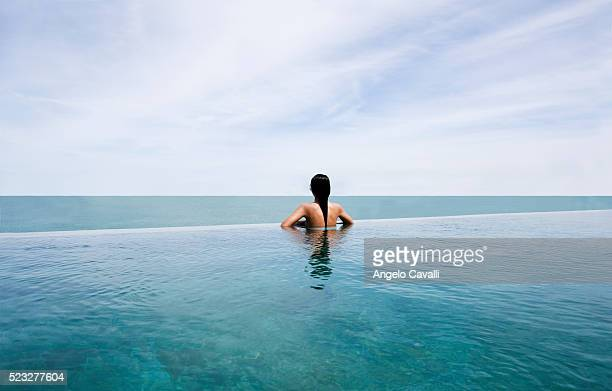 Woman in Pool Looking to the Sea and Horizon