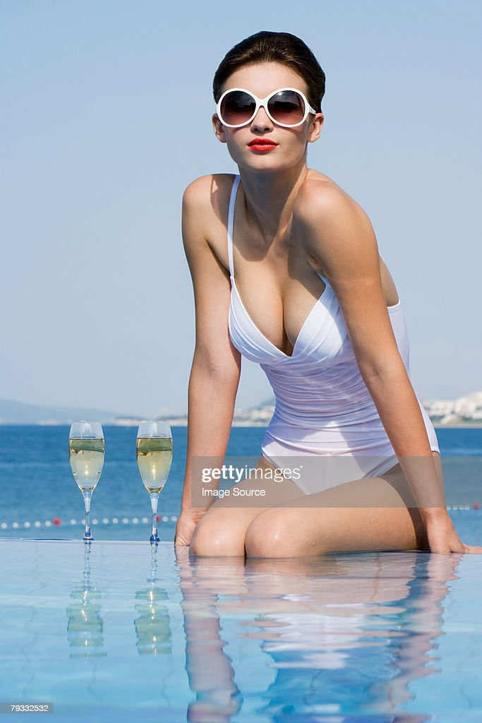 Woman in pool with champagne : Stock Photo