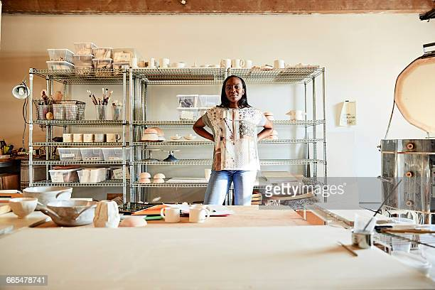 Woman in pottery studio looking at camera smiling