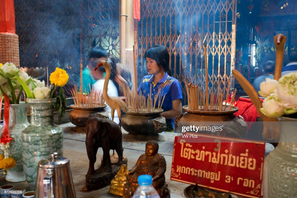 Woman in prayer holding incense sticks, Temple complex in