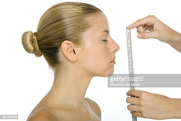 Woman in profile, face being measured with ruler