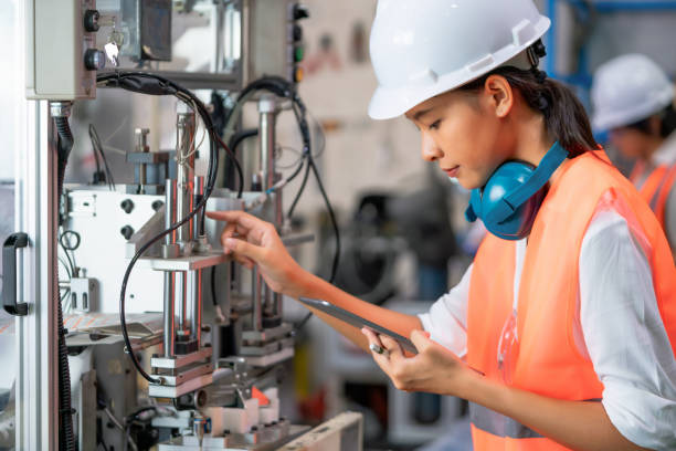 Woman in protective clothing in factory . Young electrical engineer woman using touchpad with digital tablet and standing in front of control panel working about technical problems and writes the results of measurements in manufacturing line.