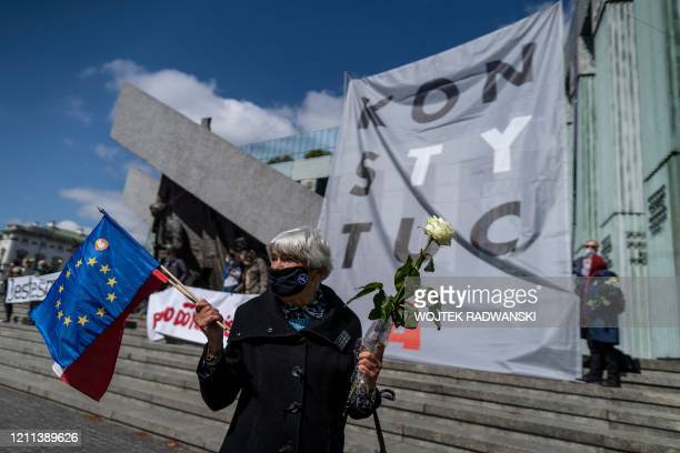 """Woman in protective face mask holding a white rose, a Polish and a European Union flag stand before a giant banner reading """"Constitution"""" in front of..."""