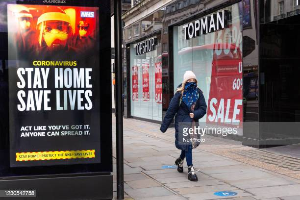 Woman in protective face mask is seen walking by the NHS 'Stay Home' poster as the UK's government introduced strict Coronavirus restrictions earlier...