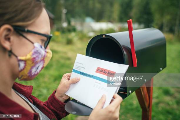 woman in protective face mask sending or receiving letter with voting ballot near a mailbox near her house - voting by mail stock pictures, royalty-free photos & images