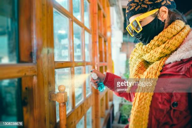 woman in protective facemask at the time of pandemic uses sanitizer. - neckwear stock pictures, royalty-free photos & images