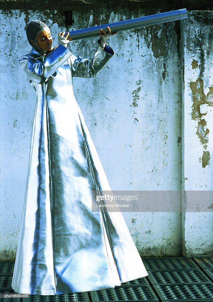 Woman in protective suit, holding metallic tube : Stockfoto