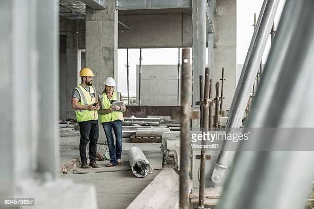 Woman in protective workwear and construction worker in construction site
