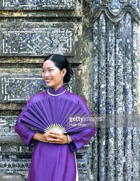 woman in purple dress holding fan - hugh sitton stock-fotos und bilder