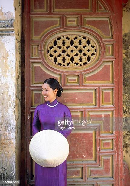 woman in purple dress standing in front of a door - hugh sitton stock-fotos und bilder