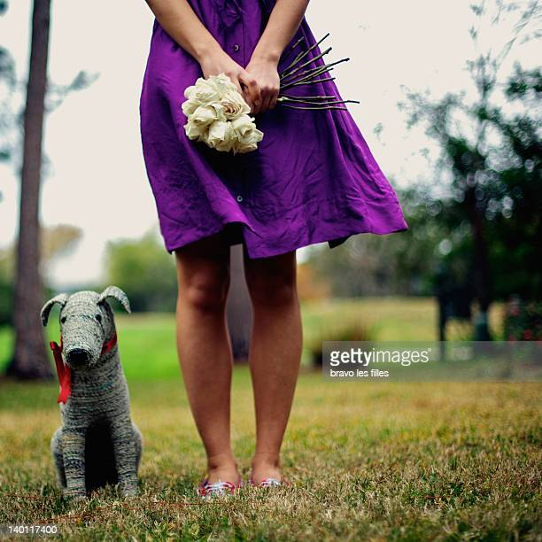 Woman in purple dress with roses and toy dog