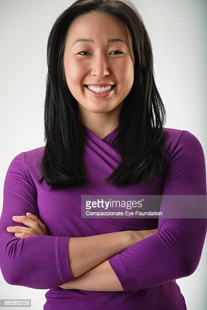 "woman in purple shirt smiling with arms crossed - ""compassionate eye"" stock-fotos und bilder"