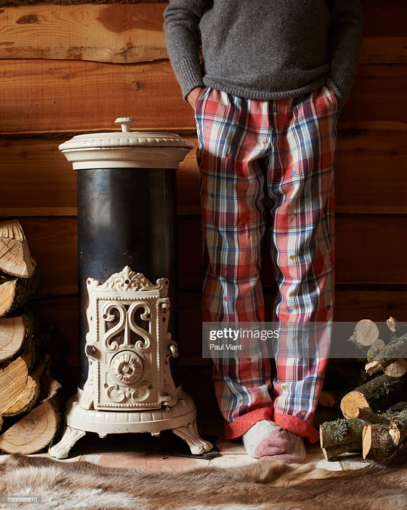 woman in pyjamas by log vintage burner : Stock Photo