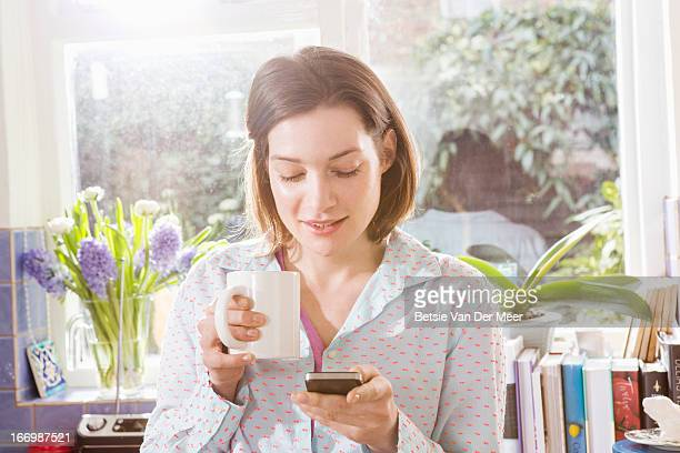 Woman in pyjamas checking mobilephone