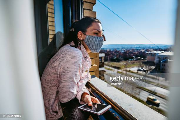 woman in quarantine looking through the window - isolamento foto e immagini stock