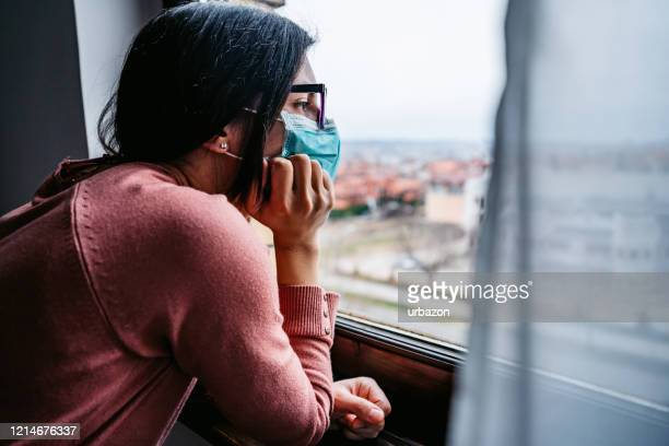 woman in quarantine looking through the window - lockdown stock pictures, royalty-free photos & images