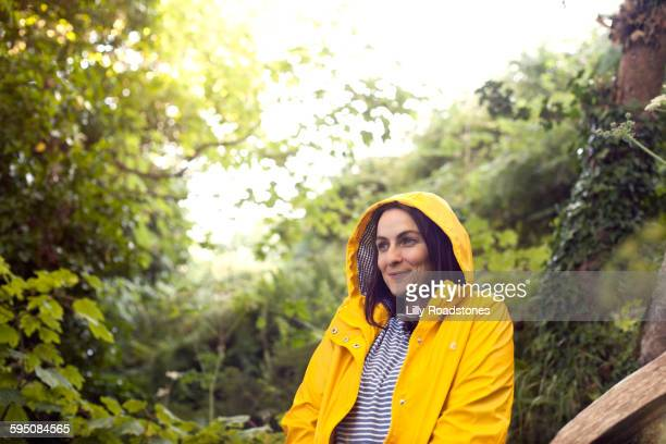 woman in rain coat in woodland area - raincoat stock pictures, royalty-free photos & images