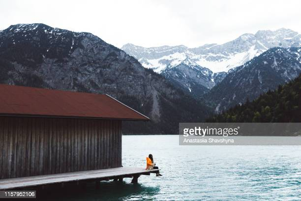 woman in raincoat and dog sitting on pier and looking at plansee and austrian alps - lakeshore stock pictures, royalty-free photos & images