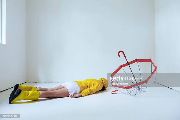 woman in raincoat and umbrella lays on the floor - pluie humour photos et images de collection