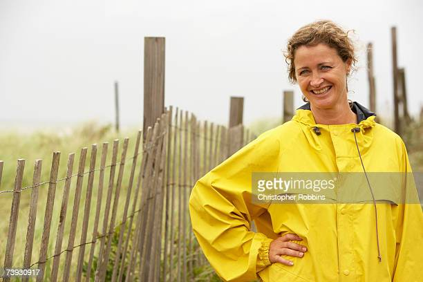 Woman in raincoat by fence, waist up