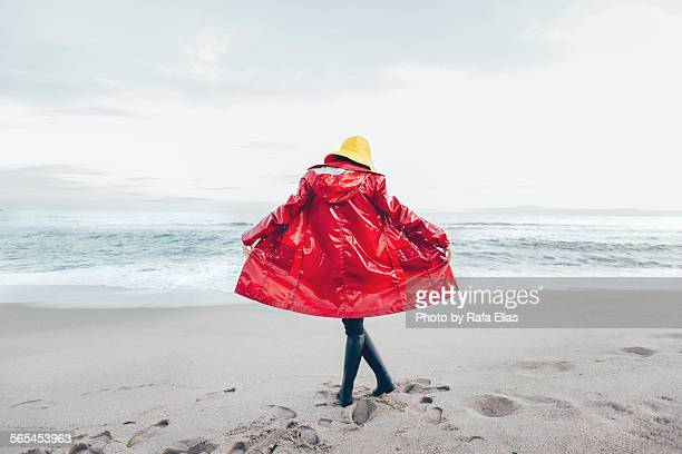 Woman in raincoat on the beach