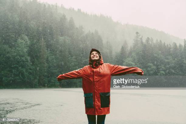 Woman in raincoat standing near the lake under the pouring rain