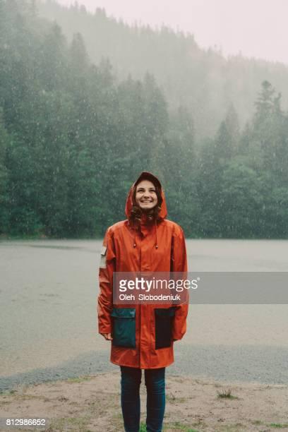 Vrouw in een regenjas reputatie in de buurt van het meer onder de stromende regen