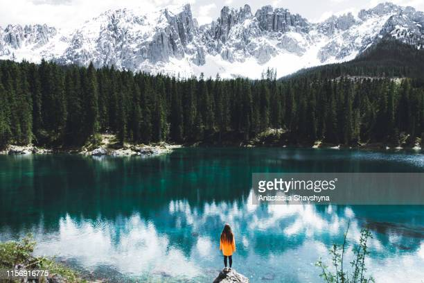 donna sotto l'impermeabile in piedi sulla roccia e guardando il lago di carezza nelle alpi dolomitiche - nature reserve foto e immagini stock