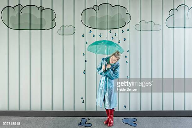 woman in rainwear under cloud painted on wall - vintage raincoat stock pictures, royalty-free photos & images