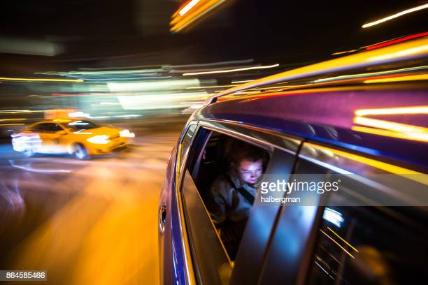 woman in rear of car driving through new york city - female streaking stock pictures, royalty-free photos & images