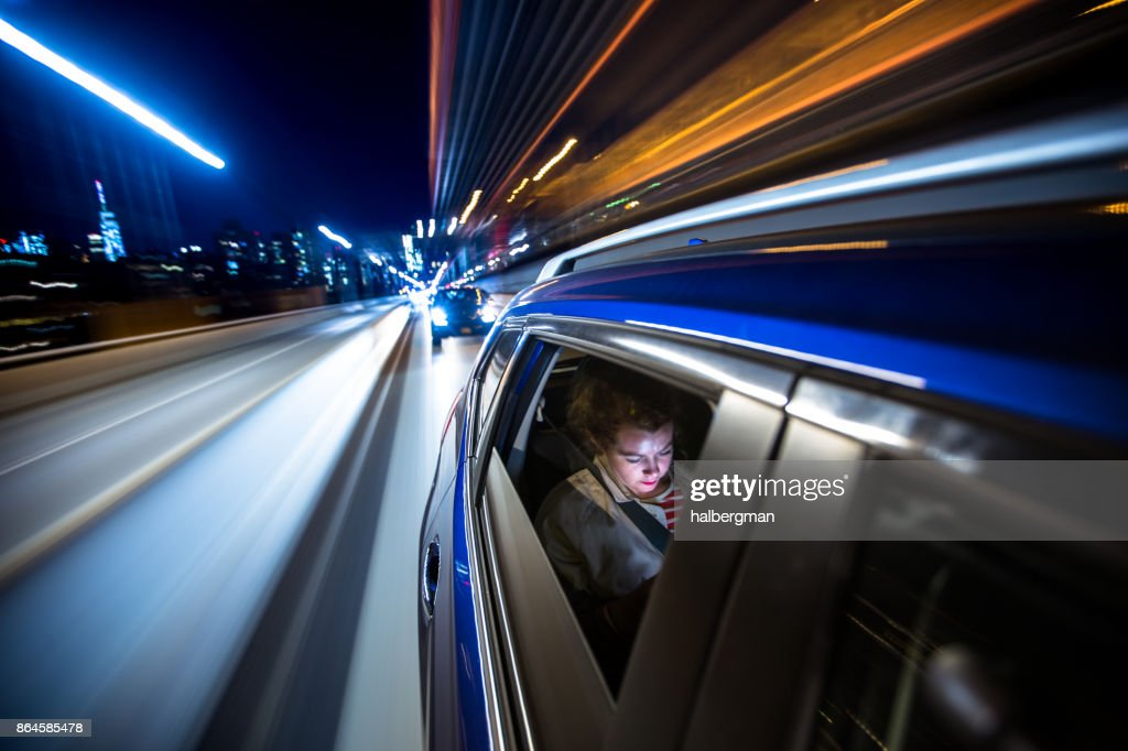 Woman in Rear of Car Driving Through New York City : Stock Photo
