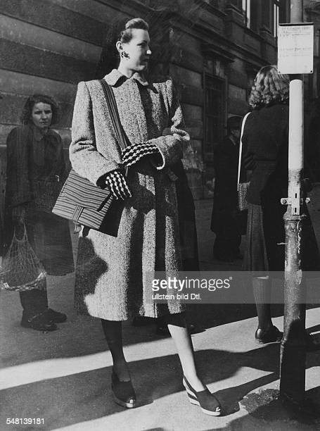 Woman in recycled clothes father's ulster bag made of carpet borders hairnet of wool oddments 1945 Photographer Regine Relang Published by 'Signal'...