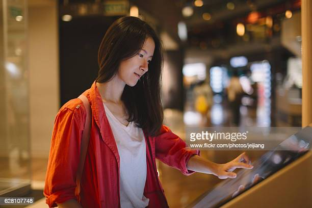 a woman in red about to touch an interactive directory guide - touch screen stock pictures, royalty-free photos & images