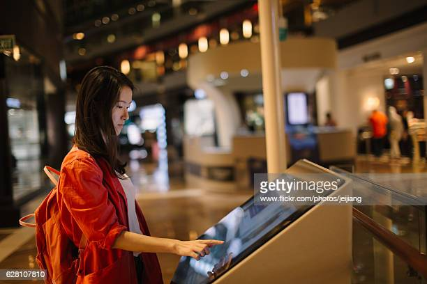 a woman in red about to touch an interactive directory guide - touch sensitive stock pictures, royalty-free photos & images