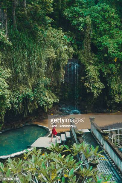 woman in red  bathrobe near the swimming pool  and waterfall - bali stock pictures, royalty-free photos & images