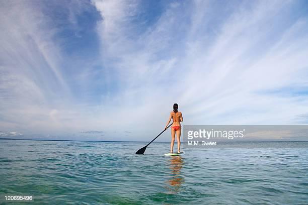 Woman in red bikini paddling